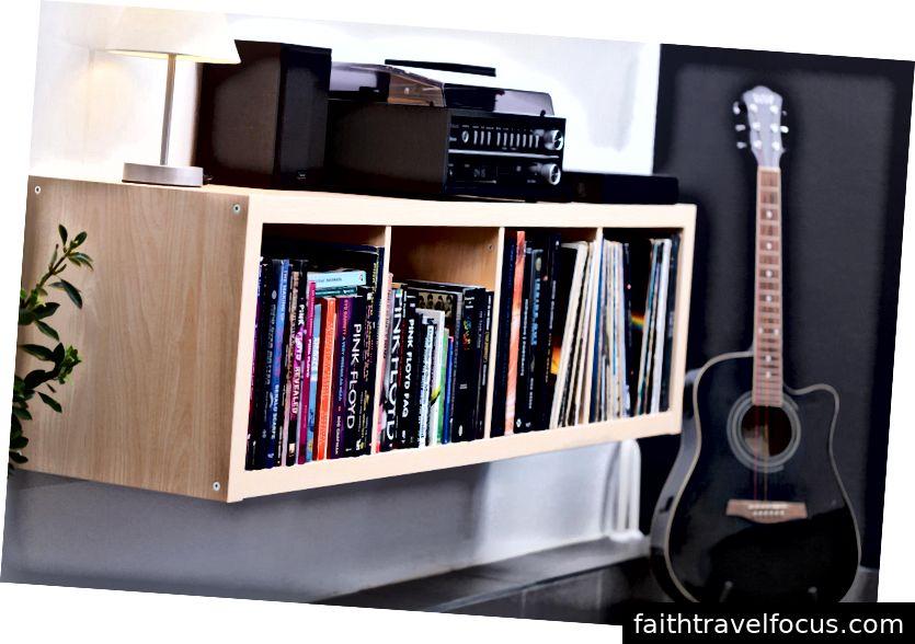 Bàn xoay với Pink Floyd LPs, hơn năm mươi cuốn sách về Pink Floyd và một cây guitar acoustic màu đen với dây màu.